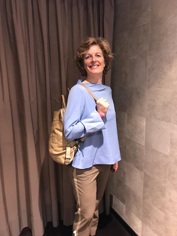Лаура в синем топе и с рюкзаком