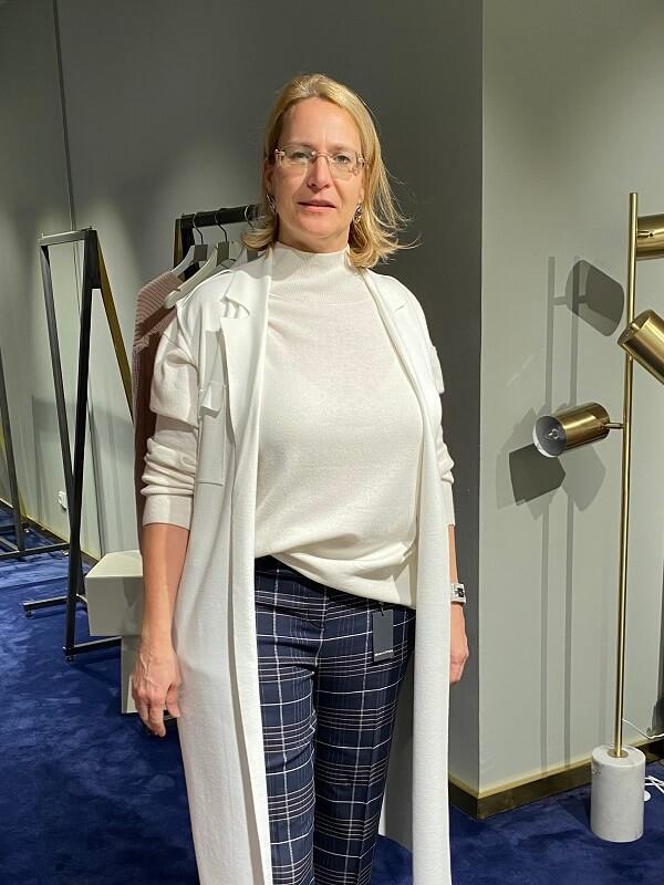 Брюки в клетку, белый свитер и вязаная желетка